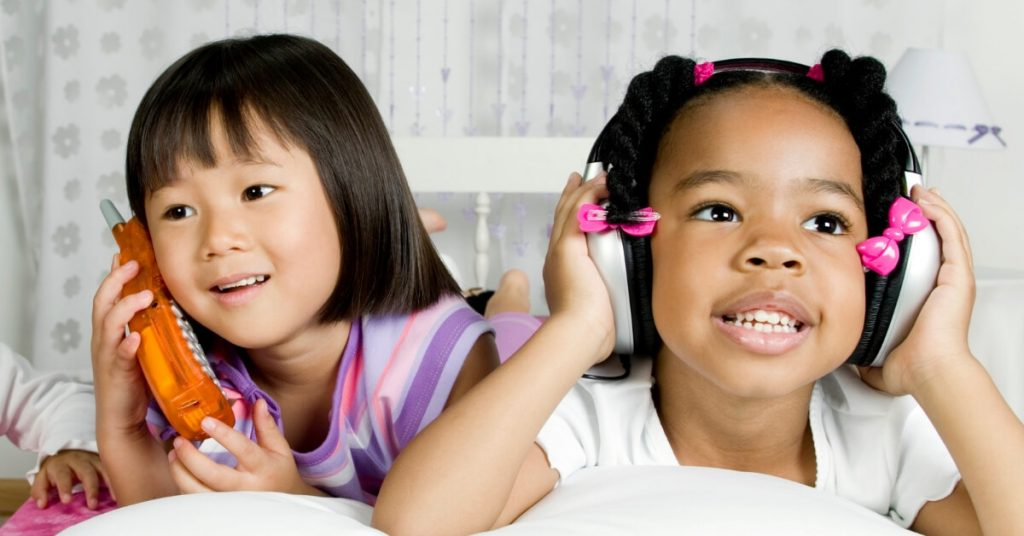 2 young girls using a play phone and headphones