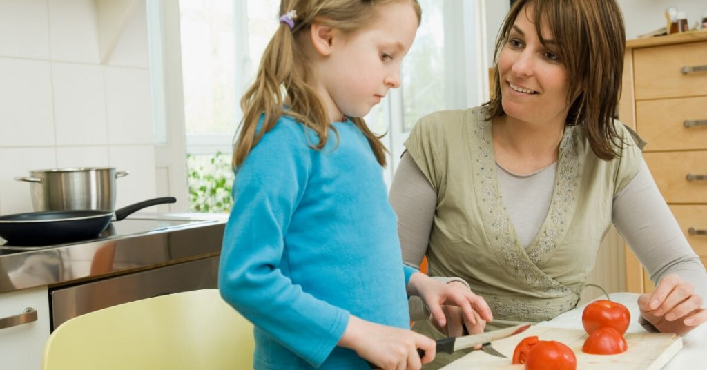 girl cutting tomatoes with her mum