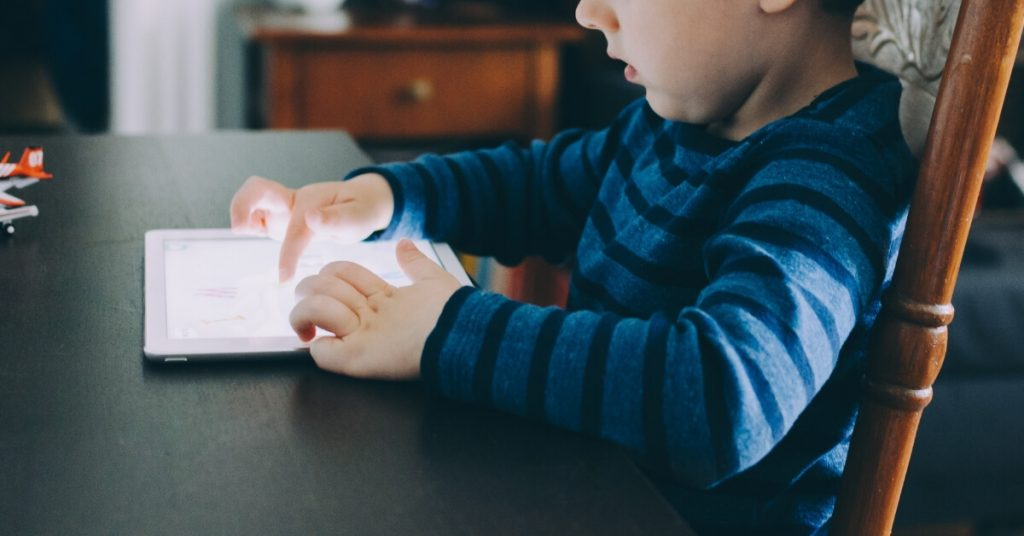 young boy playing on iPad screen