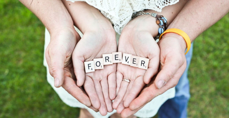Man holding womans hands holding letters spelling out forever