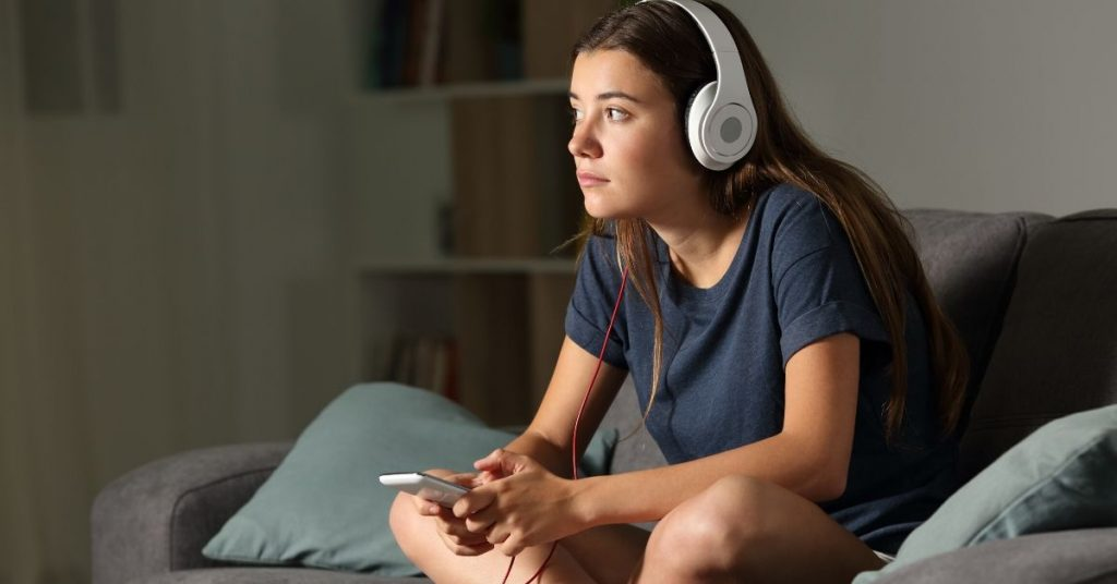 photo of girl with headphones on sitting on the couch in her home