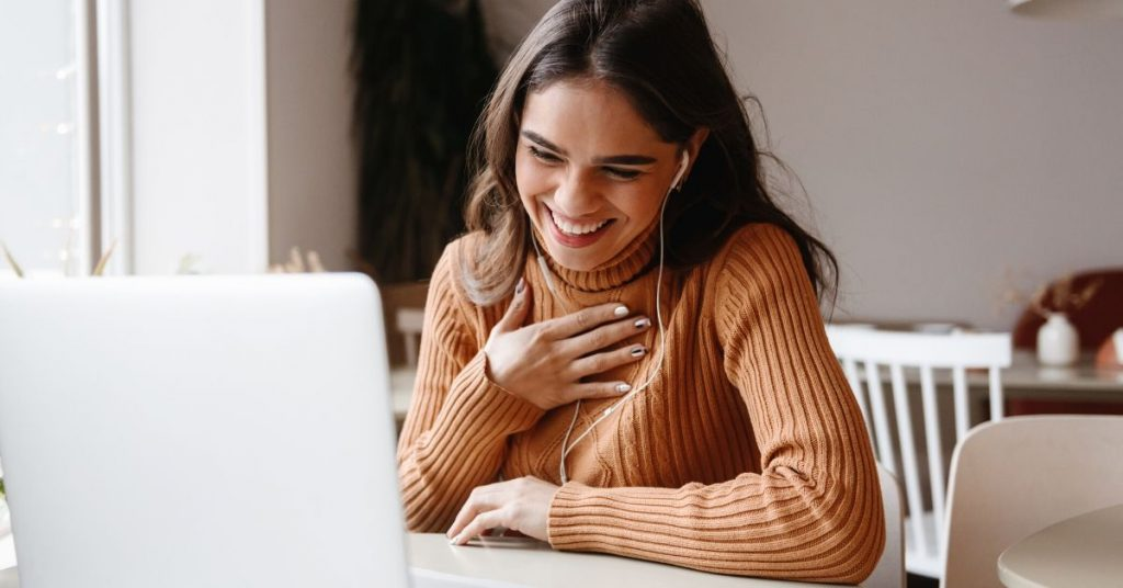 photo of woman smiling at computer
