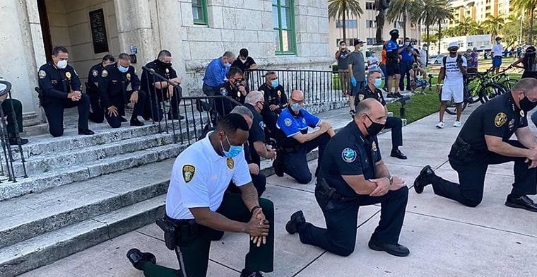 photo depicts Police taking a knee in solidarity with US protesters.