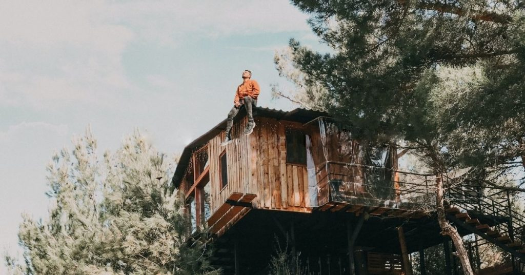 man sitting on top of a treehouse gazing upwards